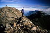 Man looking at view from main peak of Yushan mountain at Yushan National Park, Taiwan, Asia