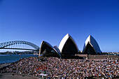 A crowd in front of the Opera House under blue sky, Sydney, New South Wales, Australia
