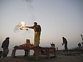 A Hindu priest performs a ritual before sunrise on the bank of the Ganga river in Varanasi, India, a sacred Hindu pilgrimage site.
