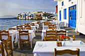 Restaurants with table and chairs in the Little Venice area overlooking the Aegean Sea in Hora on the Greek Island of Mykonos, Greece.