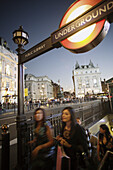 Young cosmopolitan people coming out of the underground or public subway at Piccadilly Circus, London, United Kindom, Europe