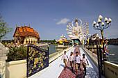 Four boys visiting Nuam Na Ram Temple, North coast, Ko Samui, Thailand
