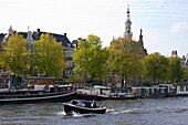 A motorboat on the river Amstel driving past some freighters, Amsterdam, Netherlands, Europe