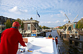 People driving a houseboat on the river Amstel, Amsterdam, Netherlands, Europe