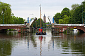 A sailing boat on the river Vecht driving past a bascule bridge, Netherlands, Europe