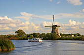 A motorboat on the river Vecht driving past a windmill, Netherlands, Europe