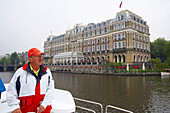 A man on a boat on the river Amstel driving past a hotel, Amsterdam, Netherlands, Europe