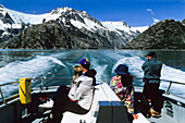 People sitting in the stern of an excursion boat, view at snow covered mountains, Inside Passage, Southeast Alaska, USA