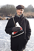 Senior man with ice skates at lake Ammersee, Upper Bavaria, Germany