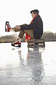 Alter Mann zieht Schlittschuhe an, Ammersee, Oberbayern, Deutschland