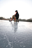 Senior man putting on ice skate, Lake Ammersee, Upper Bavaria, Germany