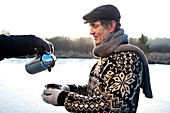 Person schenkt altem Mann Tee ein, Ammersee, Oberbayern, Deutschland