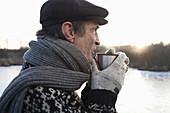 Alter Mann hält einen Becher, Ammersee, Oberbayern, Deutschland