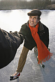Person hilft Schlittschuhläufer beim Aufstehen, Ammersee, Oberbayern, Deutschland