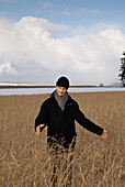 Senior man standing in dried grass, Windach, Upper Bavaria, Germany