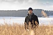 Senior man standing in winter scenery, Windach, Upper Bavaria, Germany