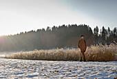 Senior man walking through winter scenery, Windach, Upper Bavaria, Germany