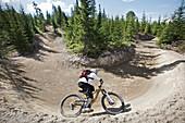 Mountainbiker riding along a steep curve, Lillehammer, Norway