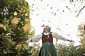 Girl wearing a dirndl, playing in autumn leaves, Kaufbeuren, Bavaria, Germany