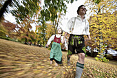 Man and a girl wearing traditional costumes running through a park, Kaufbeuren, Bavaria, Germany