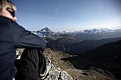 Frau sitzt auf einem Fels in den Bergen vor einem Alpenpanorama, Oberstdorf, Bayern, Deutschland