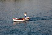 Waving fisherman in his boat, Mediterranean sea, Europe