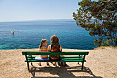 Mother and child sitting on a bench by the sea, Bol, Brac Island, Dalmatia, Croatia, Europe