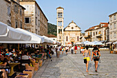 People sitting in sidewalk cafes in the Old Town of Hvar, Hvar Island, Dalmatia, Croatia, Europe