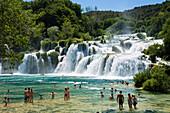 People bathing in the river at Krka waterfalls, Krka National Park, Dalmatia, Croatia, Europe
