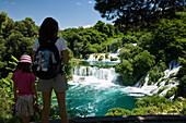 A woman and a child looking at the Krka waterfalls, Krka National Park, Dalmatia, Croatia, Europe