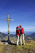 Couple embracing each other at summit cross, Kleiner Traithen, Bavarian Alps, Bavaria, Germany