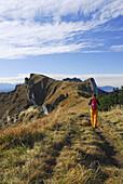 Woman hiking to Brauneck, Bavarian foothills, Bavaria, Germany