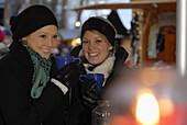 Two young woman visiting Christmas market, Frauenchiemsee, Chiemgau, Bavaria, Germany