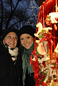Two young women visiting Christmas market, Frauenchiemsee, Chiemgau, Bavaria, Germany