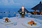A table is laid at the pool at Amankila Resort in the evening, Candi Dasa, Eastern Bali, Indonesia, Asia