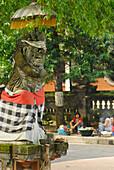 Stone figure with umbrella at Puputan Square, Denpasar, Bali, Indonesia, Asia