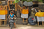 A woman on a motor scooter in front of the entrance of a house, Mas, Bali, Indonesia, Asia