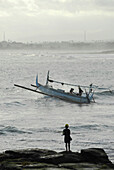 Fishing boat on the water and angler on a rock, Pekutatan, Bali, Indonesien, Asia