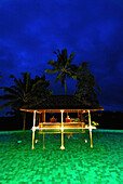 Illuminated pavilion at the pool of Amandari Resort in the evening, Yeh Agung valley, Bali, Indonesia, Asia