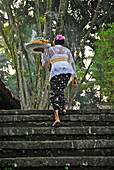 Mature woman with oblation on stairs,  Amandari Hotel, Yeh Agung, Bali, Indonesia, Asia