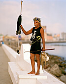 A diver with a harpoon and calamari standing at a promenade, Veracruz, Veracruz province, Mexico, America