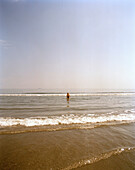 A man going into the sea for a bath, Playa Boca del Rio, Veracruz, Veracruz province, Mexico, America
