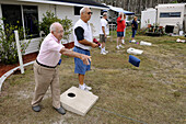 93 year old Senior retired citizens play game of bean bag toss in a recreational vechile camping park in Bonita Springs Florida