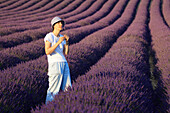 Lavender (Lavandula angustifolia), women standing in filed of Lavender, enjoying scent of Lavender, Vaucluse, Provence, France