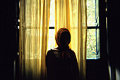 Adult, Adults, Anonymous, Back-light, Backlight, Color, Colour, Contemporary, Curtain, Curtains, Daytime, Female, Human, Indoor, Indoors, Interior, Medium shot, Medium shots, Mysterious, Mystery, One, One person, People, Person, Persons, Silhouette, Silho