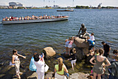 Tourists visiting the Little Mermaid bronze sculpture by Edward Eriksen erected in 1913 and based on the character created by Hans Christian Andersen. Copenhagen. Denmark.