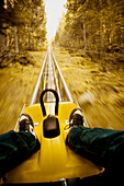 Amusement, Amusements, blurred, Color, Colour, Contemporary, Daytime, Dizziness, Dizzy, Excitement, Exciting, exterior, Fast, forest, forests, Fun, Leg, Legs, Leisure, motion, movement, moving, outdoor, outdoors, outside, Rail, Rails, Recreation, Scary, S