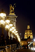The night view of Pont Alexandre III with the Dome Church of Hotel Invalides in  the background. Paris. France