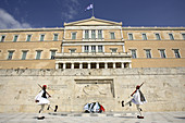 The changing of the guard ceremony in front of the Tomb of the unknow soldier with the Parliament Building in the background. Athens. Greece