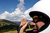 Ein Mann mit Helm hält Gleitschirm, Seiser Alm, Eisacktal, Südtirol, Italien, Europa